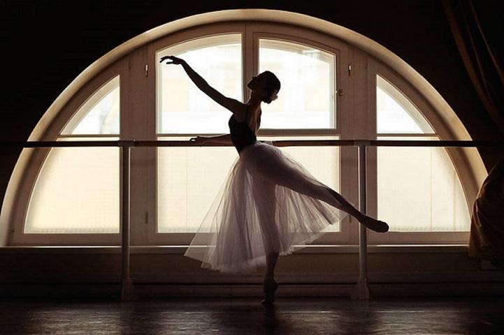 Балерина разминается на фоне окна
