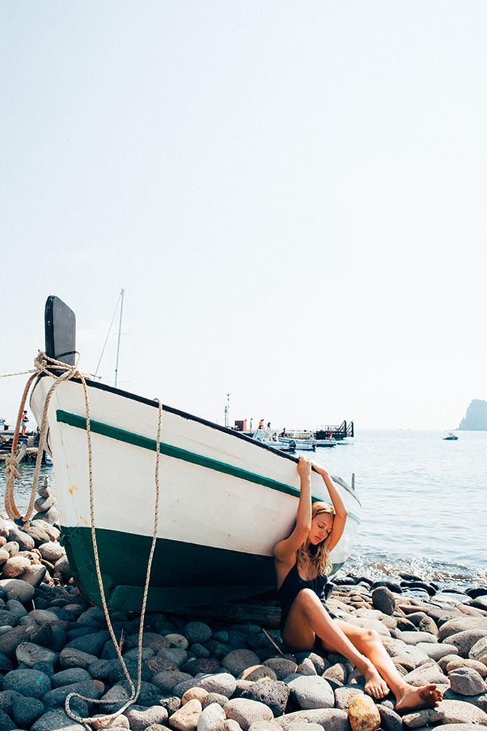 Девушка в бикини у лодки на камнях