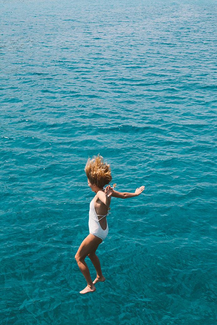 Девушка прыгает в море