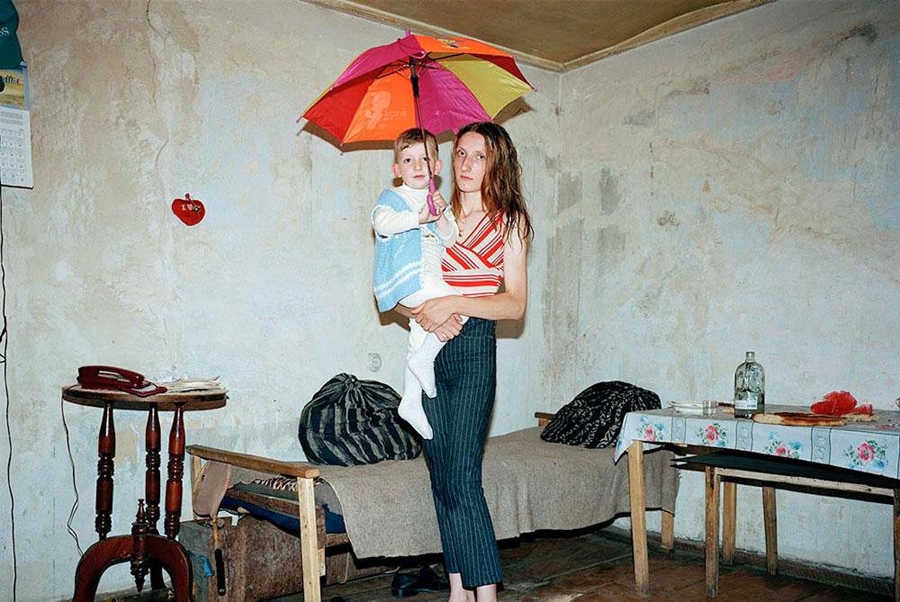 Горис, Армения. Мать с ребенком на руках в бедной комнате