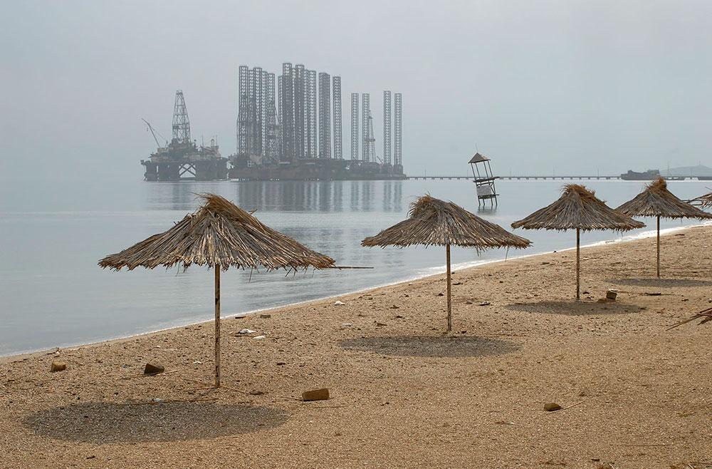 Баку, Азербайджан. Пустой пляж, пляжные зонтики, вид на нефтедобывающую платформу