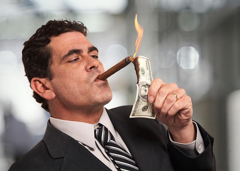 Мужчина прикуривает от денег, произвести впечатление