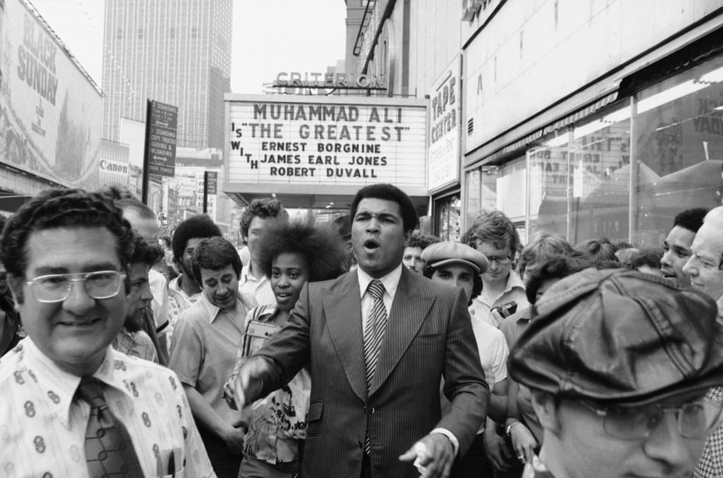 Мохаммед Али привлек внимание людей во время прогулки по Таймс-сквер в Нью-Йорке. 25 мая 1977 г.