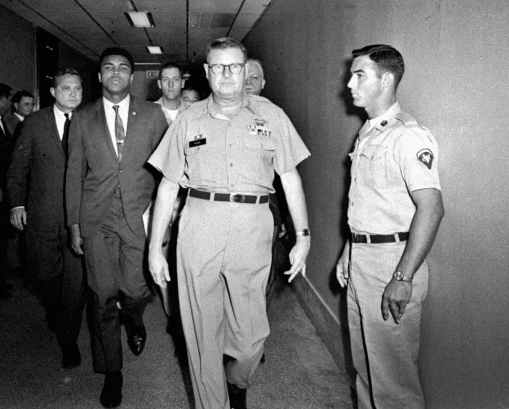 Военные конвоируют Мохаммеда Али после отказа служить в армии США. Али сообщил, что отказывается служить в армии страны
