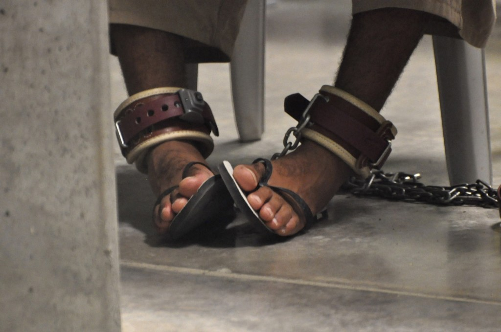A Guantanamo detainee's feet are shackled to the floor