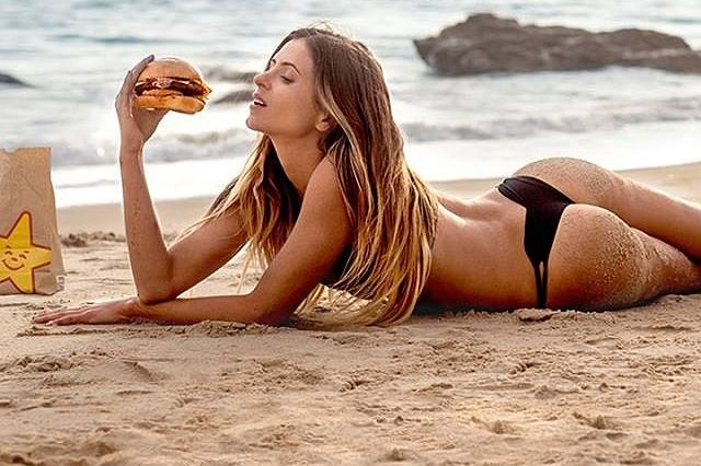 Anastasia Ashley on a beach with burger