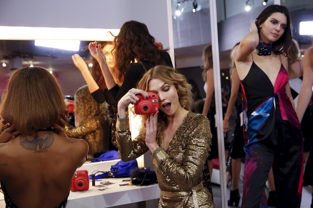 Karlie Kloss plays with a camera during a presentation for the Diane von Furstenberg Fall/Winter 2016 collection